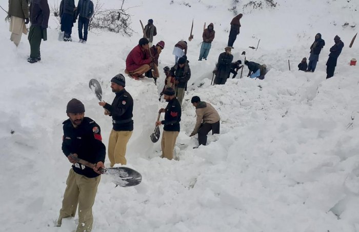 Police officers and local residents dig to search bodies of victims of avalanches in Doodnail village in Neelum Valley, Pakistan-administered Kashmir. (AP Photo)