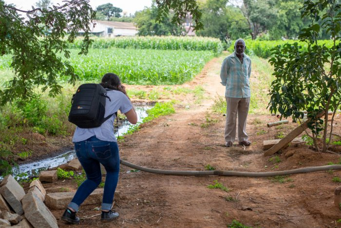 Isabella Porras, an undergraduate student from Griffith University, Brisbane in Australia, photographs a silkworm cultivator in Vijayapura in September 2019. The farmer said he uses wastewater to sustain his mulberry plants, which are fed on by silkworms,