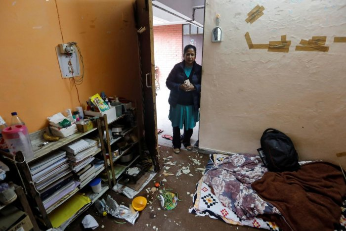 A woman looks at damaged belongings of students of Jawaharlal Nehru University (JNU) at a hostel room after it was attacked by a mob on Sunday, in New Delhi.
