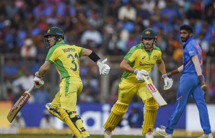 Australian batsmen Aaron Finch and David Warner (left) run between wickets while Jasprit Bumrah looks on. PTI