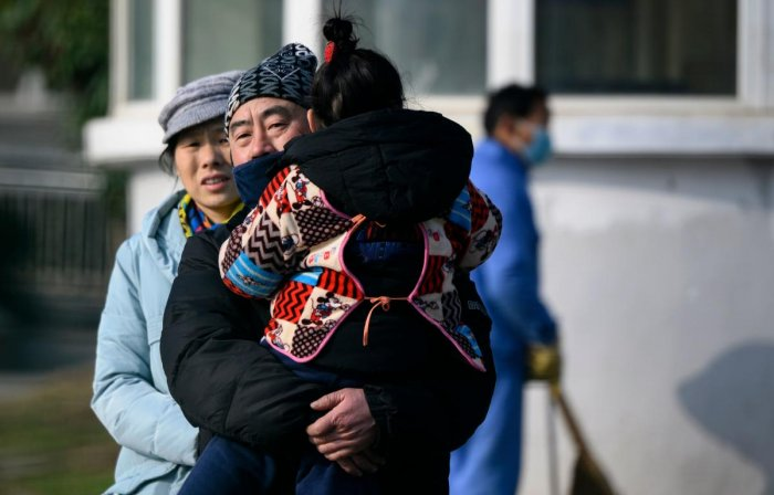 A man holding her daughter leaves the Wuhan Medical Treatment Centre, where a man who died from a respiratory illness was confined, in the city of Wuhan, Hubei province, on January 12, 2020. (AFP Photo)