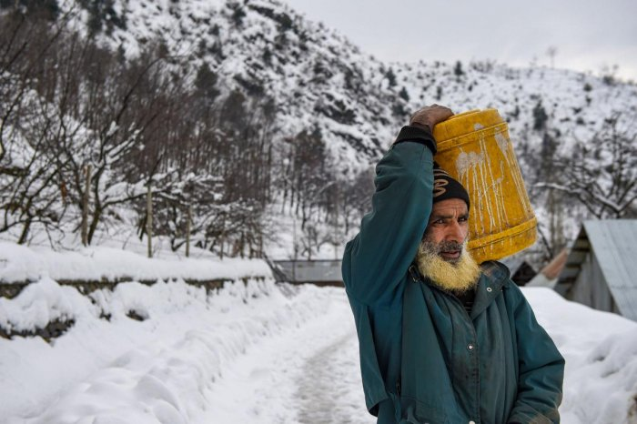 An elderly man, carrying drinking water, walks on a snow-covered road after heavy snowfall, on the outskirts of Srinagar, Tuesday, Jan. 14, 2020. (PTI Photo)