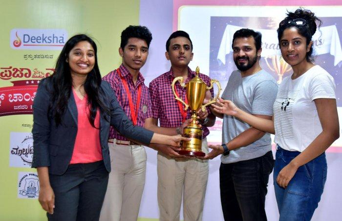 Students Prabhav and Rakshit Shetty from Little Rock Indian School, who emerged as champions in PV-DH Quiz championship, receive the trophy from Actors Vijay Raghavendra and Greeshma at Vishweshatheertha Rangamandira in Vidyodaya Public School on Thursday