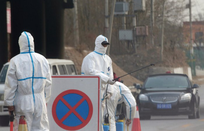 Workers in protective suits are seen at a checkpoint on a road leading to a village near a farm where African swine fever was detected, in Fangshan district of Beijing, China November 23, 2018. 9Ruters Photo)