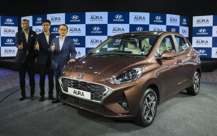 Hyundai Motors India MD & CEO SS Kim (R), Executive Director Sales and Marketing DH Park (C) and Director -Sale and Marketing Tarun Garg (L) pose for photographs with the newly launched sedan Hyundai Aura, in New Delhi, Tuesday, Jan. 21, 2020. (PTI Ph
