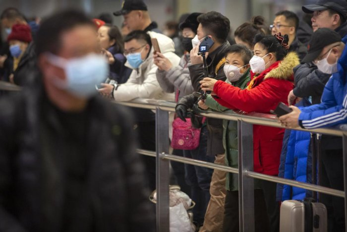 People wear face masks as they wait for arriving passengers at Beijing Capital International Airport in Beijing, Thursday, Jan. 23, 2020. (PTI Photo)