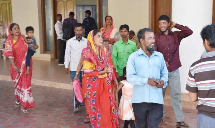 Migrant labourers come out of Crystal Hall after police verification of their identity documents, in Madikeri on Thursday. DH Photo