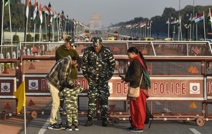 A child, donned in army uniform, interacts with security personnel standing guard at the Rajpath, which is all-set for the Republic Day Parade, in New Delhi. (PTI Photo)
