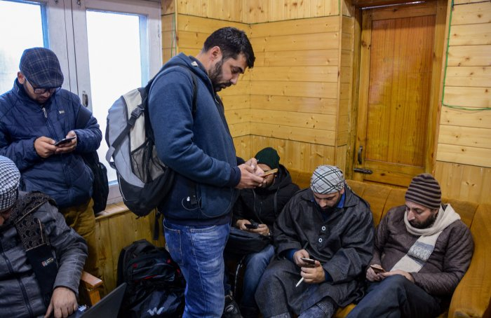 Journalists uses their mobile phone as government orders for the restoration of pre-paid mobile services and 2G internet services in 2 districts of the Kashmir valley after the six months of ban, at Government Media Facilitation Centre in Srinagar, Saturday, Jan. 18, 2020. (PTI Photo)
