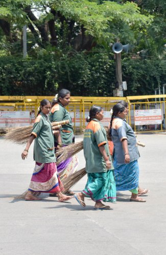 BBMP pourakarmikas are seen out side the Mount Carmel College counting centre, in Bengaluru on Thursday. (Photo/ B H Shivakumar)