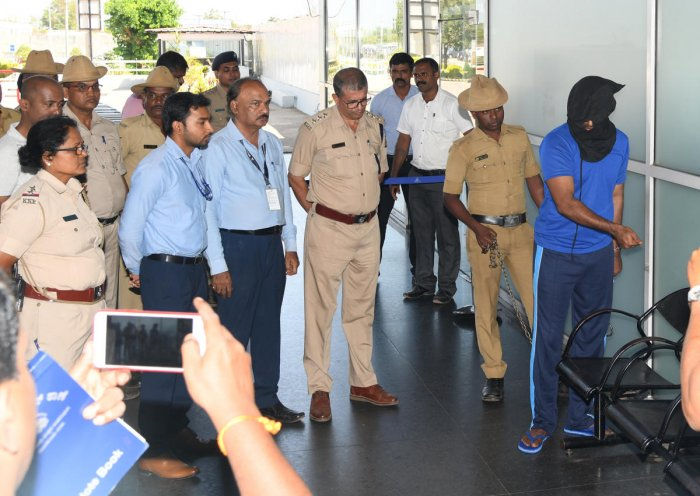 Adithya Rao reconstructs sequences to show how he placed a bag containing crude bomb on the chair near the entrance of departure gate at Mangaluru Airport on Friday. DH Photo