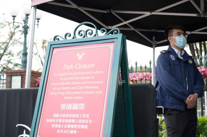 A member of staff wearing a mask stands next to a sign announcing the park's closure at Hong Kong Disneyland in Hong Kong on January 26, 2020, after it announced it was shutting its doors until further notice over a deadly virus outbreak in central China.