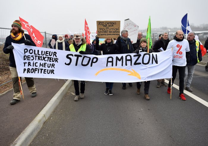 Protesters hold banners and placards during a demonstration against the installation of a warehouse of the online retailer Amazon on the former military air base of Frescaty. (AFP Photo)