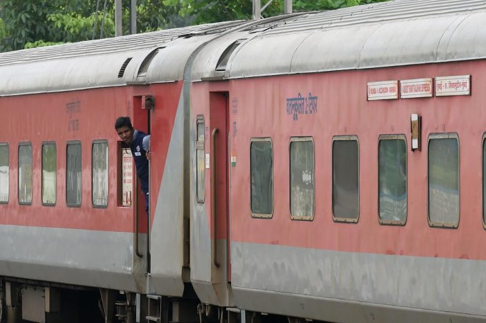 An Indian railway worker looks out from a long distance passenger train as it approaches a platform in Mumbai on July 5, 2019. (Credit: AFP Photo)