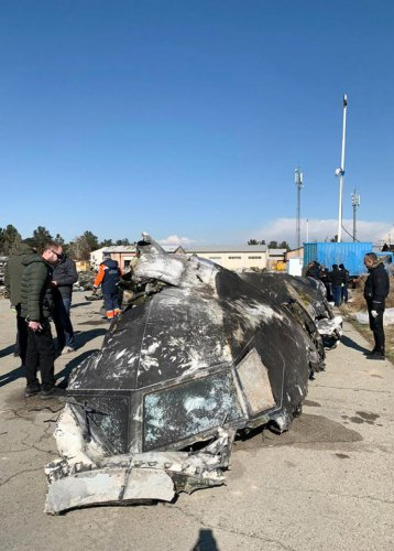 People standing and analysing the fragments and remains of the Ukraine International Airlines plane Boeing 737-800 that crashed outside the Iranian capital Tehran on January 8, 2020. (Credit: AFP Photo)