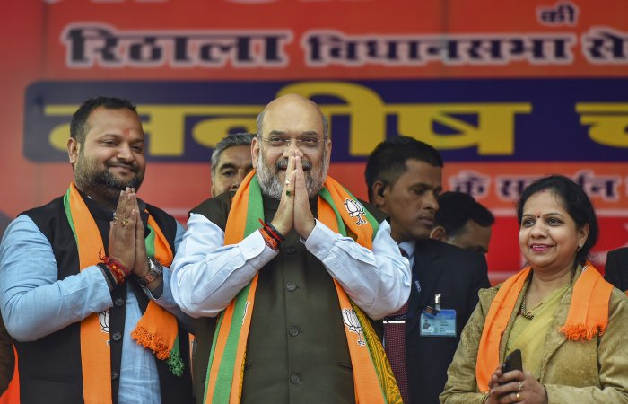Union Home Minister and BJP leader Amit Shah (C) with party candidate Manish Choudhary (L) during an election campaign ahead of the forthcoming Delhi Assembly elections, at Rithala constituency in New Delhi, Monday, Jan. 27, 2020. (Credit: PTI Photo)