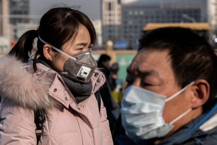 A woman wearing a protective mask walks past a paramilitary police officer (R) outside Beijing railway station in Beijing on January 21, 2020. Credit: AFP Photo