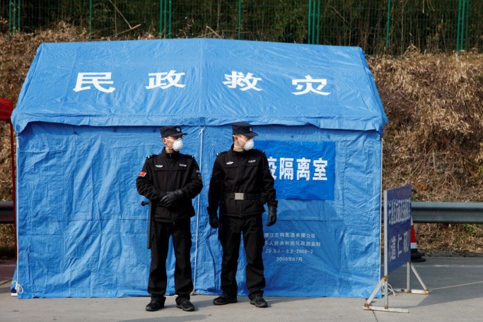 Security personnel stand in front of a disaster relief tent at a checkpoint in Yunxi county