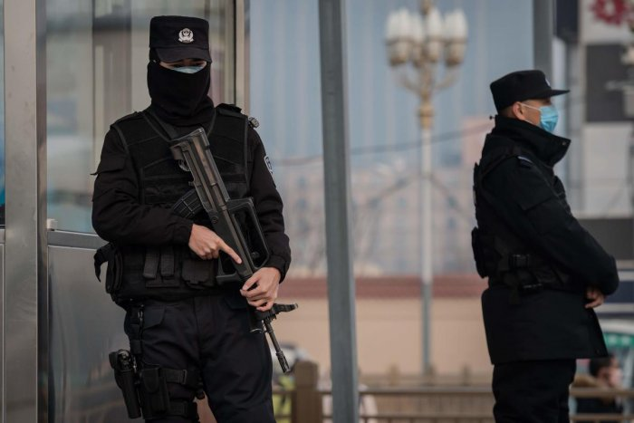 In this picture taken on January 27, 2020 police officers wearing protective facemasks to help stop the spread of a deadly virus which began in Wuhan, secure an area at the Beijing railway station