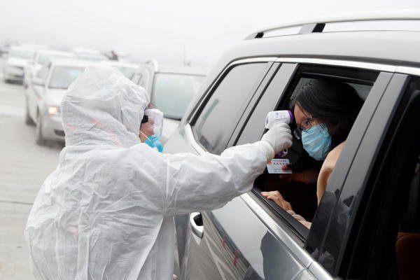 A medical worker in protective suit checks the body temperature of a car passenger at a checkpoint outside the city of Yueyang (Reuters Photo)