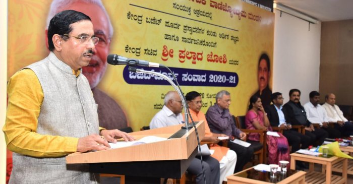 Union minister Pralhad Joshi speaks at the pre-budget interaction programme held at the KCCI hall at J C Nagar in Hubballi on Monday. (PTI Photo)