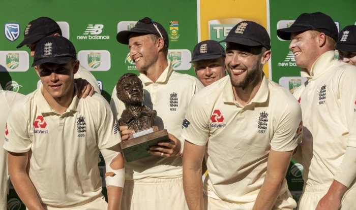 England's captain Joe Root, center, with teammates pose for photographers after receiving their trophy at the end of day four of the fourth cricket test match between South Africa and England at the Wanderers stadium in Johannesburg, South Africa, Monday,