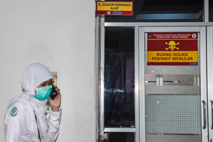 An Indonesian medical worker speaks on her phone outside an isolation area, to be occupied by patients showing symptoms of a deadly virus outbreak which began in the Chinese city of Wuhan, at a public hospital in Mataram, West Nusa Tenggara on January 28,