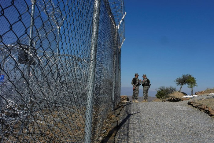 Pakistani soldiers talk as they stand near a security fence at the border post in Torkham, Pakistan. (Reuters file photo)