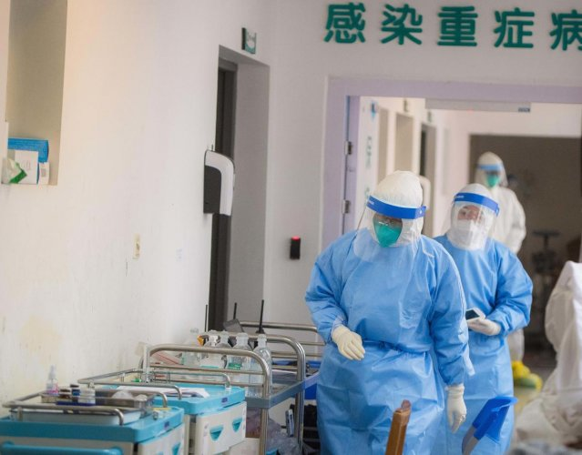 In this photo released by China's Xinhua News Agency, medical personnel wearing protective suits work in the department of infectious diseases at Wuhan Union Hospital in Wuhan in central China's Hubei Province