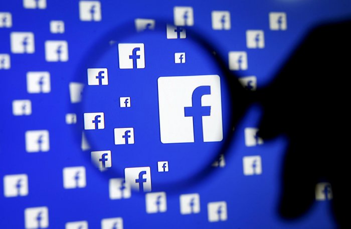 A man poses with a magnifier in front of a Facebook logo on display in this illustration taken in Sarajevo, Bosnia and Herzegovina. (Reuters photo)