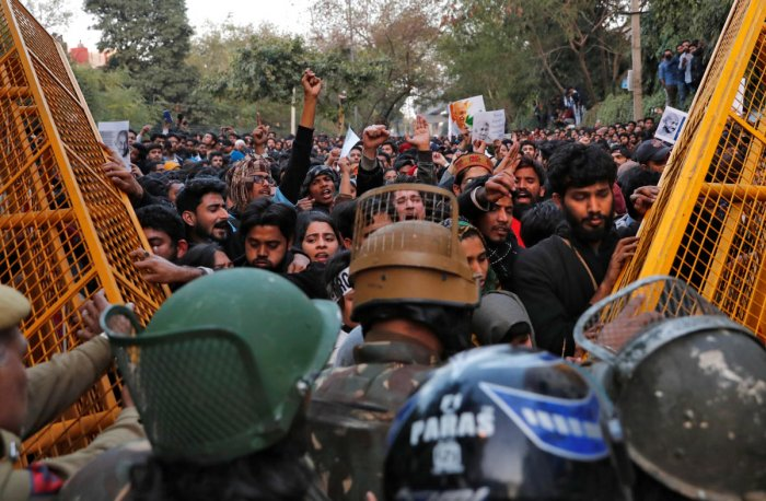 Demonstrators try to remove police barricades during a protest against a new citizenship law outside the Jamia Millia Islamia university in New Delhi. (Reuters Photo)