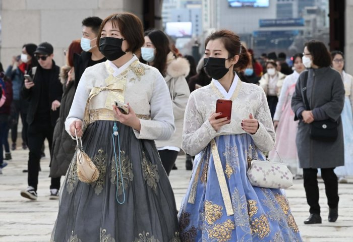 Tourists in traditional Korean hanbok dress wear face masks as they visit at Gyeongbokgung palace in Seoul