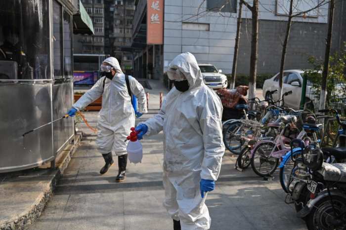 """People dressed in protective clothes disinfect an area in Wuhan, in Hubei province on January 30, 2020. - The World Health Organization, which initially downplayed the severity of a disease that has now killed 170 nationwide, warned all governments to be """"on alert"""" as it weighed whether to declare a global health emergency."""