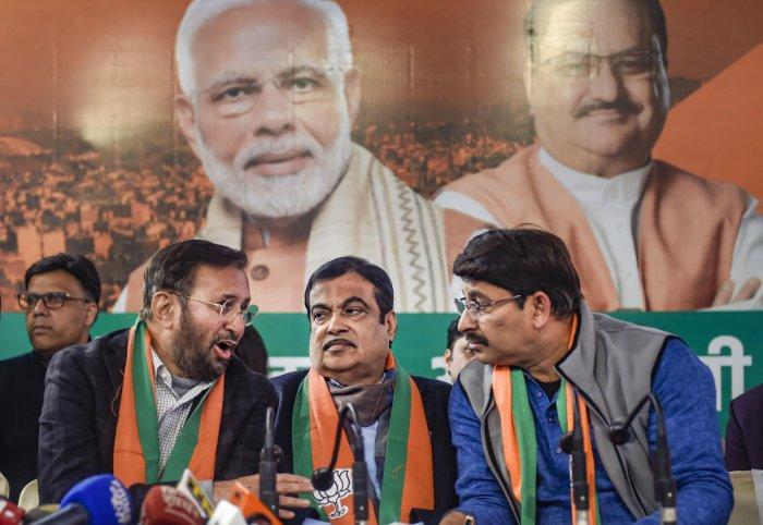 Union ministers and BJP leaders Nitin Gadkari (C) and Prakash Javadekar (L) with Delhi BJP President Manoj Tiwari at the release of the 'BJP Sankalp Patra for Delhi Assembly Elections 2020, in New Delhi, Friday, Jan. 31, 2020. (PTI Photo)