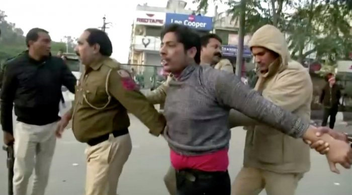 Police officers detain a man, who identified himself as Kapil Gujjar, who fired multiple shots at a site where people were protesting against a new citizenship law in New Delhi