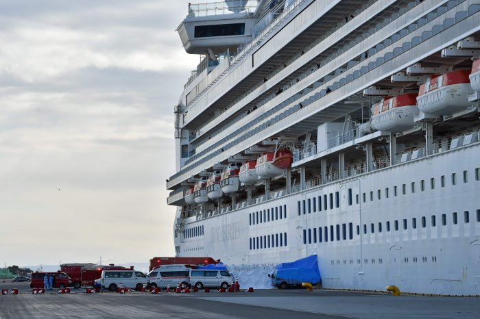 An ambulance (L) waits for patients who tested positive for the new coronavirus from the Diamond Princess cruise ship (R) at the Daikoku Pier Cruise Terminal in Yokohama. (AFP Photo)
