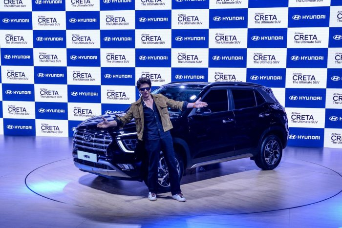 Bollywood actor Shah Rukh Khan gestures as he poses next to the newly launched Hyundai Creta SUV at the Auto Expo 2020 at Greater Noida