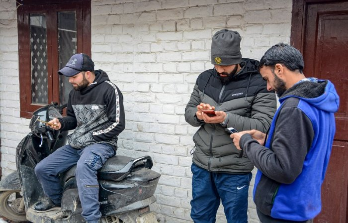 ouths use internet service on their mobile phones after government restored 2G mobile internet services, in Srinagar. (PTI Photo)