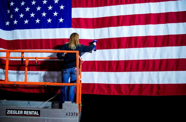 A woman takes the wrinkles from a flag before Pete Buttigieg, Democratic presidential candidate and former South Bend, Indiana mayor attends a watch party on Caucus Day in Des Moines, Iowa, U.S., February 3, 2020. (Reuters Photo)