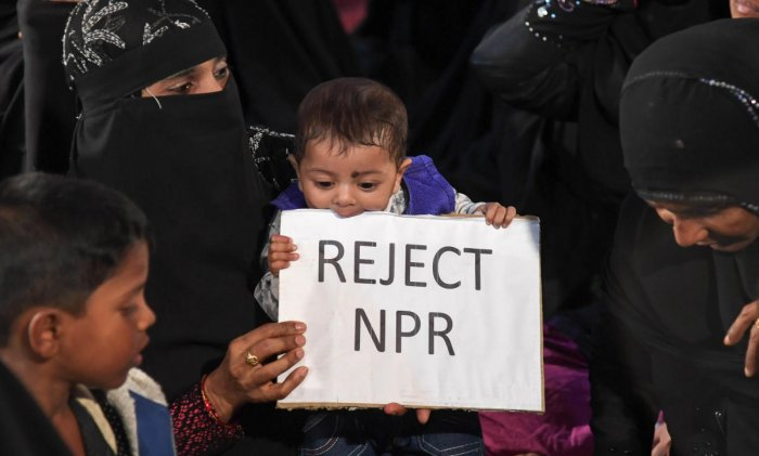 A child holds a placard against the National Population Register during the rally. DH PHOTO/B H SHIVAKUMAR
