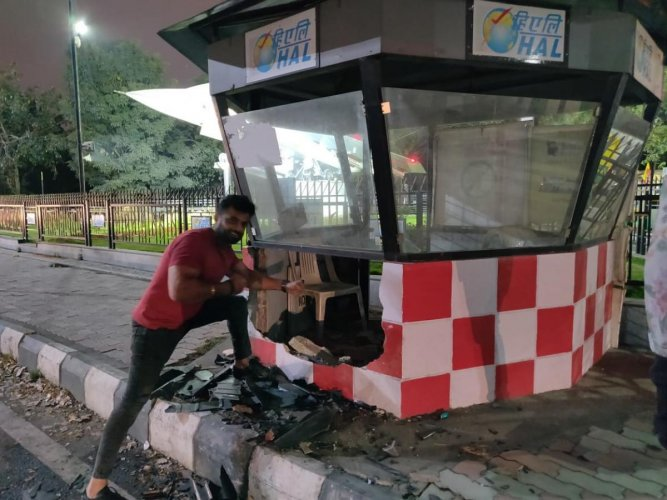 Sunny Sabharwal poses with the damaged kiosk at Minsk Square.