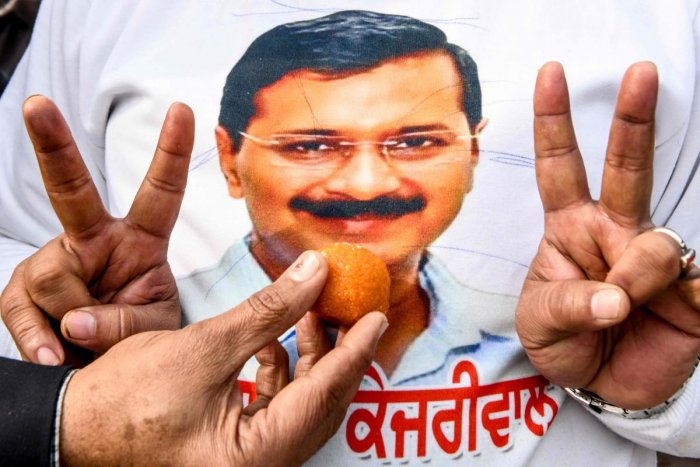 Aam Aadmi Party (AAP) workers offer sweets to eachother as one of them wears a t-shirt showing the face of AAP chief Arvind Kejriwal to celebrate victory following the early results of New Delhi regional assembly election, in Amritsar on February 11, 2020