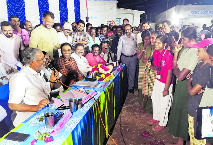 Primary and Secondary Education Minister S Suresh Kumar interacts with children, during his overnight stay at Pachechedoddi village of Hanur taluk, on Monday.