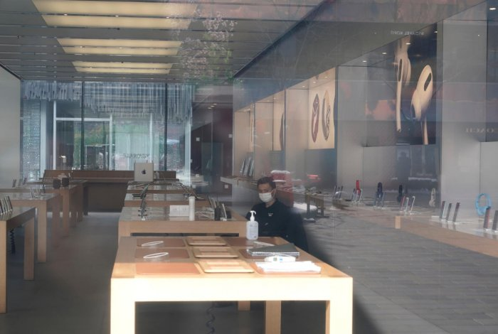 Security personnel wearing a face mask is seen in a closed Apple store at Sanlitun in Beijing. Reuters