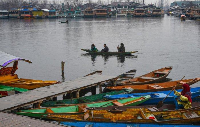 A boatwoman rows her boat across Dal Lake during light rain, in Srinagar, Tuesday, Jan. 28, 2020. (PTI Photo)
