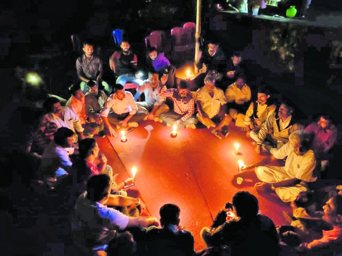 As the power supply got disrupted at the protest venue in front of the grampanchayat premises in Siddapura on Tuesday night, the flood victims continued their dharna urging for permanent rehabilitation, in candlelight. DH Photo