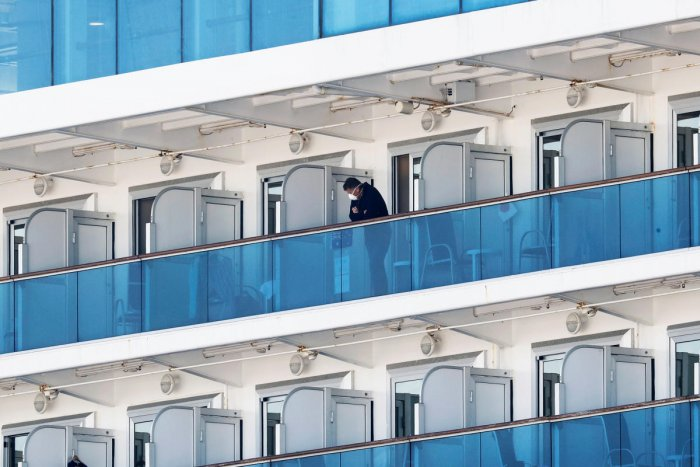 A passenger wearing a mask stands at the balcony of his cabin on the cruise ship Diamond Princess, as the vessel's passengers continue to be tested for coronavirus, at Daikoku Pier Cruise Terminal in Yokohama, south of Tokyo, Japan February 13, 2020. REUTERS/Kim Kyung-Hoon