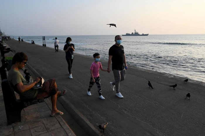 Tourists wearing protective face masks to help stop the spread of a deadly virus which began in Wuhan, walk along Galle Face Green promenade in Colombo. (AFP Photo)