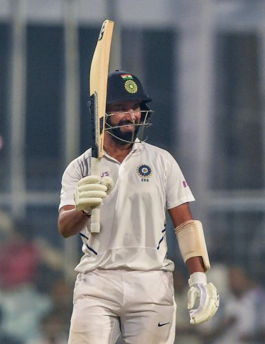 Indian batsman Cheteswar Pujara raises his bat after complete his half century during 1st day of 1st Day-night Pink ball Test match against Bangladesh at Eden Garden in Kolkata, Friday, Nov. 22, 2019. (PTI Photo)