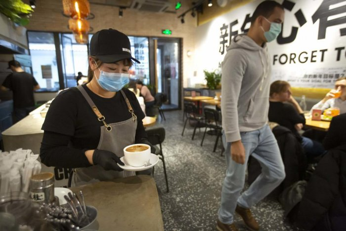 A server wearing a face mask carries a cup of coffee at a Moka Bros cafe in Beijing, Friday, Feb. 14, 2020. (AP Photo)